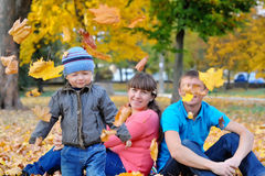Young family with a child walks in autumn park Royalty Free Stock Image