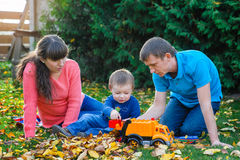 Young family with a child walks in autumn park Stock Images