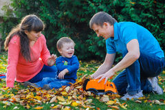 Young family with a child walks in autumn park Royalty Free Stock Photos