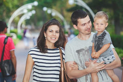 Young family with child walks in summer alley Stock Images