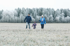Young family with  child walks in winter field Stock Photography