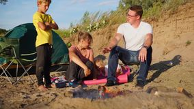 Young family with a child is warming around a fire and tents on nature in summer stock footage