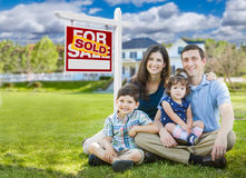 Young Family With Kids In Front of Custom Home and Sold For Sale Sign. Young Family With Children In Front of Custom Home and Sold For Sale Real Estate Sign Royalty Free Stock Photography