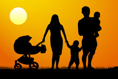 A young family with children  silhouette at sunset. A man and a woman with two children Stock Photo