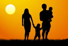 A young family with children silhouette at sunset Stock Photo