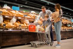 Young Family Choosing Bread in Supermarket. Full length portrait of happy young family shopping for groceries in supermarket together with little boy, while stock image