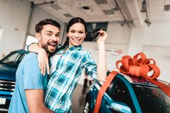 Young Family Are Choosing A New Car In Showroom. Staring At Each Other. Automobile Salon. Make A Decision. Gift Ribbon. End Of A Deal. Good Offer. Happy royalty free stock photography