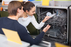 Young family choosing new dish washing machine in supermarket Royalty Free Stock Images