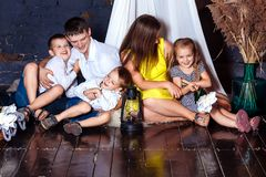 Young family cockloft home children mother father kids sit loft five attic laugh happy hugging girl boy floor royalty free stock images