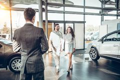 Young family comes into Car dealership to choose the car to buy it stock photo