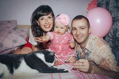 Young family consisting father, mother and little daughter in the room stock photography