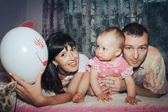 Young family consisting father, mother and little daughter in the room stock photo