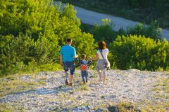A young family consisting of mom, dad and child are walking down the stones from the mountain stock photography
