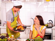 Young family cooking chicken at kitchen Stock Images