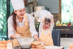 Young family cooking food in kitchen. Happy young girl with her mother mixing batter in the bowl stock images