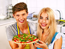 Young family cooking pizza at kitchen. Royalty Free Stock Images
