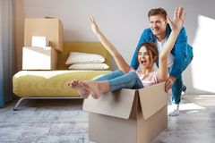 Young family couple bought or rented their first small apartment. Cheerful happy people having fun. She sit in box and. Scream. Guy move her. Moving and royalty free stock images