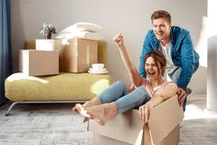 Young family couple bought or rented their first small apartment. Cheerful woman scream sitting in box. Guy move her royalty free stock images