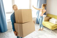Young family couple bought or rented their first small apartment. Guy carry heavy boxes alone. Young woman stand at stock photography