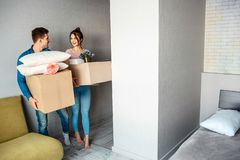 Young family couple bought or rented their first small apartment. Happy excited people look at each other. They hold stock images