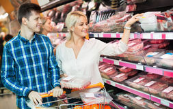 Young family couple choosing chilled meat Stock Photography
