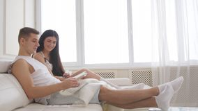 Young family couple - man and woman sitting together on the couch and spending time at home stock photography