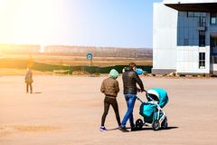 Young family couple with mom and dad are walking outdoors with a baby stroller of blue color in which the newborn child in a large royalty free stock images