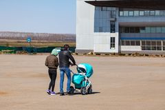 Young family couple with mom and dad are walking outdoors with a baby stroller of blue color in which the newborn child in a large stock photos