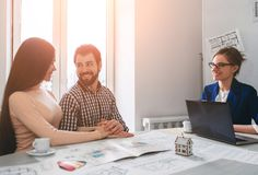 Young family couple purchase rent property real estate . Agent giving consultation to man and woman. Signing contract. Young family couple purchase rent property Royalty Free Stock Images