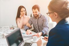 Young family couple purchase rent property real estate . Agent giving consultation to man and woman. Signing contract. Young family couple purchase rent property Stock Image