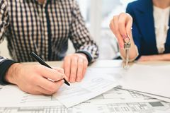 Young family couple purchase rent property real estate . Agent giving consultation to man and woman. Signing contract. Young family couple purchase rent property Royalty Free Stock Photos