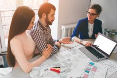 Young family couple purchase rent property real estate . Agent giving consultation to man and woman. Signing contract. Young family couple purchase rent property Royalty Free Stock Image