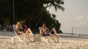 Young family couple sunbathing and drinking colored cocktail on tropical beach. Lovers on honeymoon on exotic vacation stock video