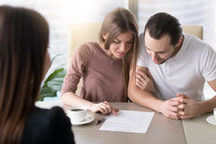 Young family couple taking loan, studying contract agreement bef. Smiling family couple reading contractual terms before signing contract, examining documents to stock image