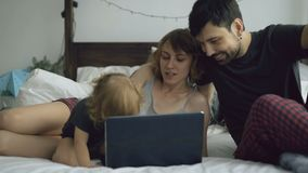 Young family with cute little girl playing with daughter while she typing on laptop computer sitting in bed at home. In the morning stock footage