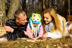 Young family with a daughter in autumn nature Royalty Free Stock Photo