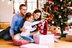 Young family with daughter at Christmas tree at home. Stock Photos
