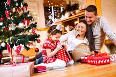 Young family with daughter at Christmas tree at home. Stock Photo