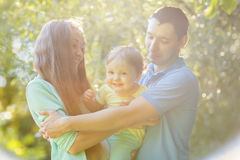 Young family with daughter hugging in park Royalty Free Stock Photography