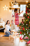Young family with daugter at Christmas tree at home. Royalty Free Stock Images