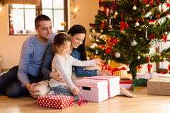 Young family with daugter at Christmas tree at home. Stock Images