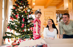 Young family with daugter at Christmas tree at home. Stock Photo