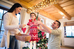 Young family with daugter at Christmas tree at home. Stock Photos