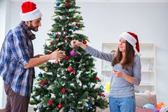 The young family decorating christmas tree on happy occasion Royalty Free Stock Images