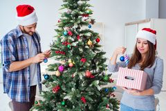 The young family decorating christmas tree on happy occasion Stock Images