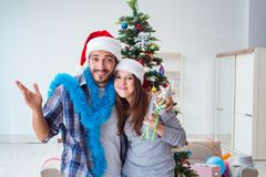 The young family decorating christmas tree on happy occasion Stock Image