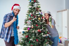 The young family decorating christmas tree on happy occasion Royalty Free Stock Image