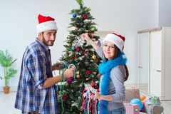 The young family decorating christmas tree on happy occasion Stock Photos