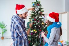 The young family decorating christmas tree on happy occasion Stock Photography