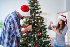 The young family decorating christmas tree on happy occasion Royalty Free Stock Photo